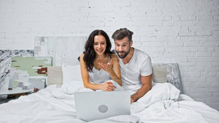 excited woman pointing with hand at laptop while watching movie with boyfriend in bed