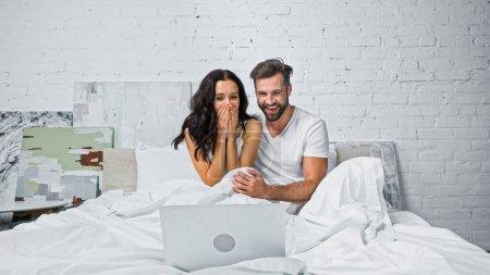 aufgeregte Frau, die Mund mit Händen bedeckt, während sie mit ihrem lachenden Freund Comedy auf dem Laptop anschaut