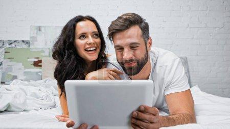 Aufgeregte Frau lacht neben lächelndem Freund mit digitalem Tablet im Schlafzimmer