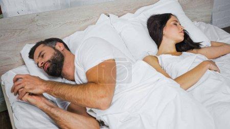 Photo pour Homme barbu messagerie sur smartphone tout en étant couché près de petite amie endormie - image libre de droit