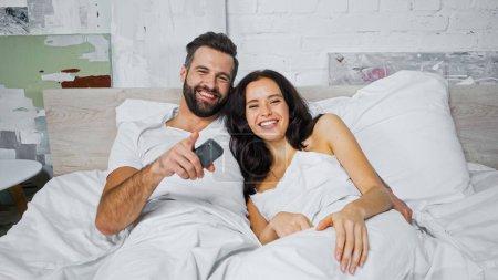 Photo pour Homme joyeux pointant du doigt tout en regardant la télévision avec petite amie dans la chambre - image libre de droit
