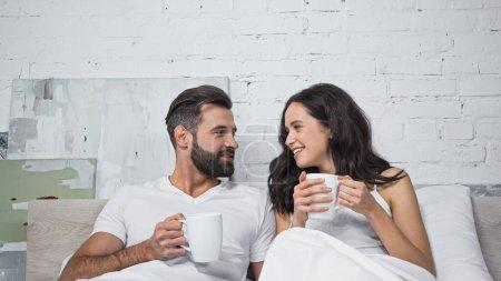 Photo pour Homme gai et femme regardant l'autre tout en tenant des tasses de café au lit - image libre de droit