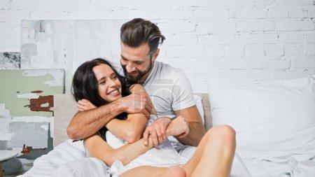 Photo pour Heureux jeune couple embrassant tout en s'amusant dans la chambre - image libre de droit