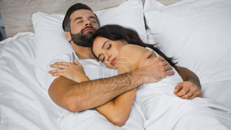 Photo pour Jeune couple étreignant tout en dormant sur la literie blanche - image libre de droit