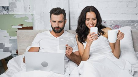 smiling woman chatting on smartphone near man using laptop in bed
