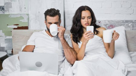 young couple drinking coffee and using gadgets in bedroom