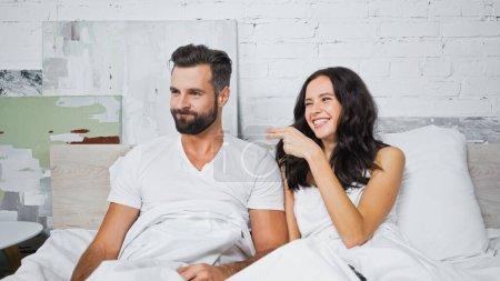 joyful brunette woman pointing at discouraged boyfriend in bedroom