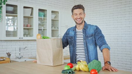 Photo for Smiling man looking at camera near fresh vegetables and paper bag in kitchen - Royalty Free Image