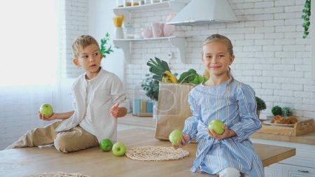 Photo pour Souriante fille avec des pommes assis sur la table de cuisine près du frère et sac en papier - image libre de droit