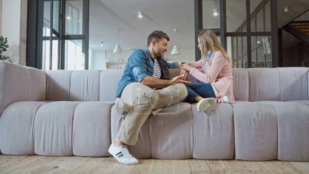 Husband talking with wife on couch at home