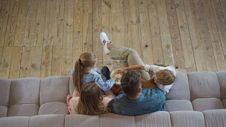 Photo for Overhead view of family taking popcorn on sofa at home - Royalty Free Image