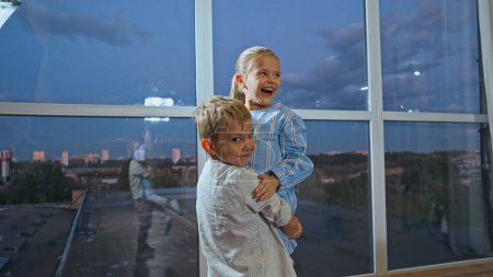 Photo pour Garçon souriant étreignant sœur joyeuse à la maison - image libre de droit