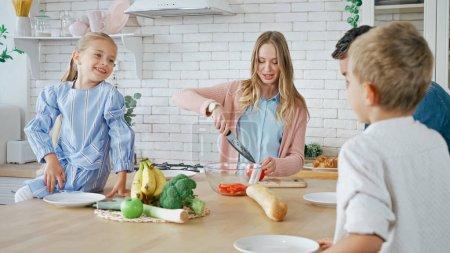 Photo pour Fille souriante assise près de la mère coupant la salade et la famille sur le premier plan flou dans la cuisine - image libre de droit