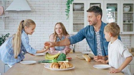 Photo pour Père donnant baguette à la fille près de la famille dans la cuisine - image libre de droit