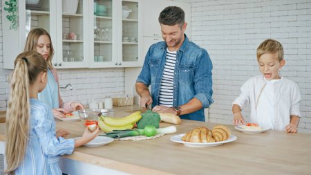Smiling father cutting baguette near family in kitchen