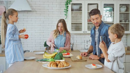 Family with smartphone and food standing near table in kitchen