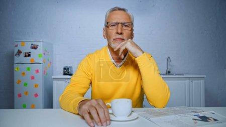 Senior mit Brille blickt in die Kamera neben Tasse Kaffee und Zeitung auf verschwommenem Vordergrund