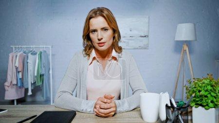 Photo pour Femme regardant la caméra alors qu'elle était assise près du carnet et de la tasse sur la table à la maison - image libre de droit