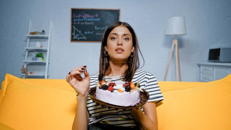 Woman in striped t-shirt holding sweet cake on couch