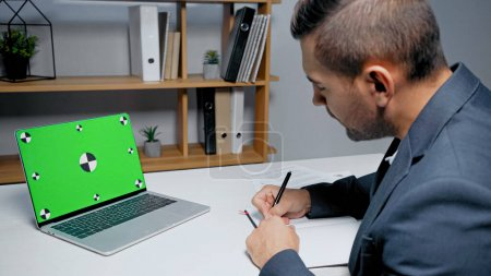 Laptop with green screen near businessman writing in notebook on blurred foreground