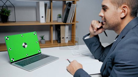Laptop with chroma key near businessman with pen and notebook on blurred foreground