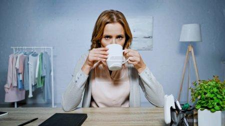 Photo pour Femme boire du thé et regarder la caméra à la maison - image libre de droit