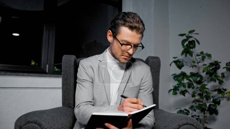 Photo for Young businessman writing on notebook on armchair in office - Royalty Free Image