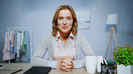 Photo for Adult woman smiling at camera near cup and plant on table - Royalty Free Image
