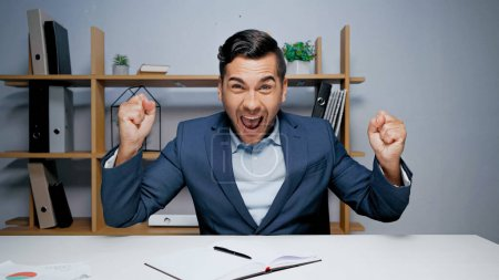 Photo for Excited businessman showing yes gesture during video chat in office - Royalty Free Image