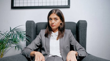 Brunette manager sitting on armchair near plant