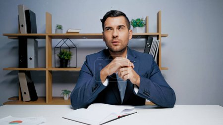 Photo for Thoughtful businessman sitting near notebook in office - Royalty Free Image