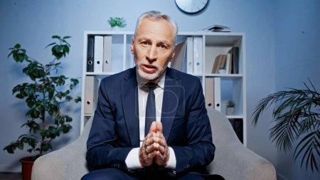 Photo pour Homme d'affaires âgé avec des mains priantes parlant à la caméra lors d'un appel vidéo au bureau - image libre de droit