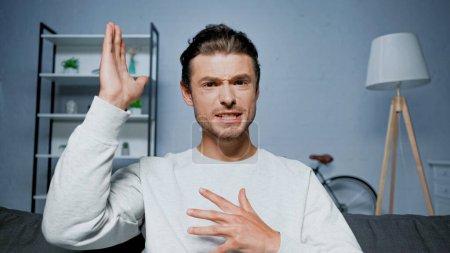 Photo pour Jeune homme avec expression du visage parlant et gesticulant lors d'un appel vidéo - image libre de droit