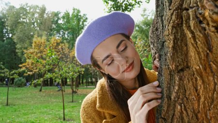 happy young woman smiling while touching tree trunk in park