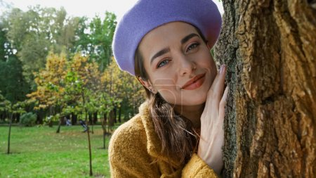 Photo for Joyful woman in trendy beret looking at camera while leaning on tree trunk in park - Royalty Free Image