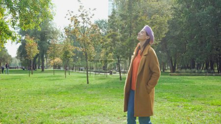 young woman with closed eyes enjoying walk in autumn park