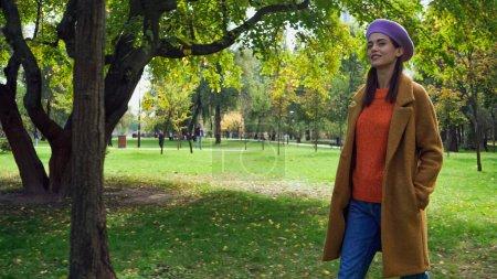 Photo pour Femme heureuse en tenue d'automne élégant se promener dans le parc avec la main dans la poche - image libre de droit
