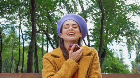 excited woman laughing with closed eyes while holding ripe apple in park
