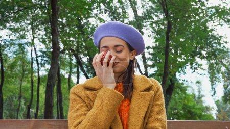 Photo pour Femme heureuse sentant la pomme mûre avec les yeux fermés dans le parc - image libre de droit