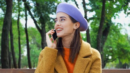 Photo for Happy stylish woman looking away while calling on mobile phone in autumn park - Royalty Free Image