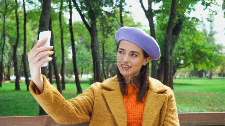 Photo for Happy woman in autumn outfit taking selfie on mobile phone in park - Royalty Free Image