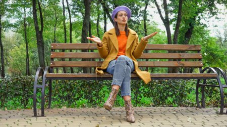 offended woman showing shrug gesture while waiting on bench in park