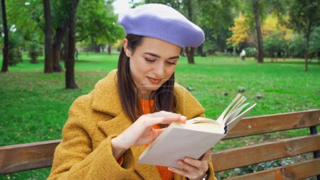 smiling woman in trendy autumn outfit reading book in park