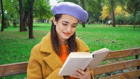 Photo pour Jeune femme élégante souriant tout en lisant le roman dans le parc d'automne - image libre de droit