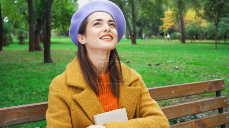 cheerful woman in beret looking up while sitting with book in park
