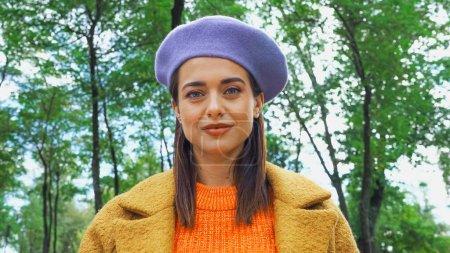 Photo pour Jeune femme au béret branché regardant la caméra dans le parc - image libre de droit