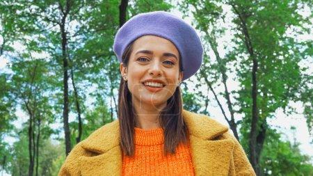 alegre mujer de moda sonriendo a la cámara en el parque de otoño