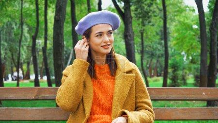 Photo pour Femme souriante fixer écouteur tout en étant assis sur le banc dans le parc d'automne - image libre de droit