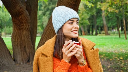 Photo for Happy woman in knitted beanie holding mug of warm drink in park - Royalty Free Image
