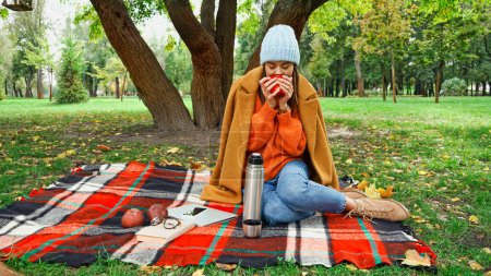 woman in autumn outfit drinking warm tea on plaid blanket in park